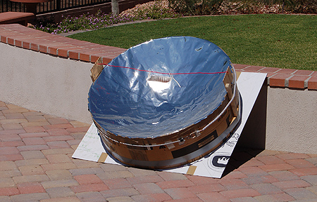 Parabolic Solar Oven. Cardboard, tape, glue, wood, wire and chrome vinyl. You can clearly see the aluminum cooking pan glowing and reflecting a portion of the suns energy hitting it.
