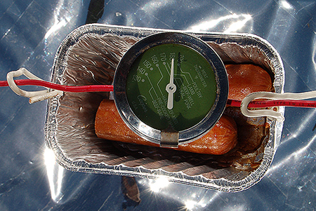 Thermometer, inserted into a hot-dog, most likely touching the bottom cooking surface of the suspended pan.